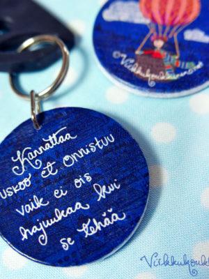 Pyöreä puinen Suomessa valmistettu Virkkukoukkusen suunnittelema sininen avaimenperä tekstillä.