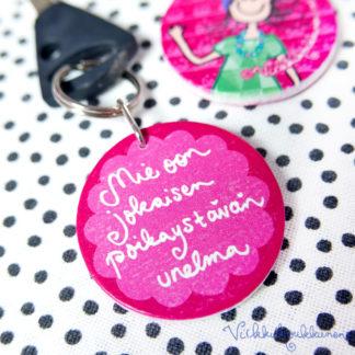 """Pyöreä puinen Suomessa valmistettu Virkkukoukkusen suunnittelema pinkki avaimenperä """"Mie oon jokaisen poikaystävän unelma"""" - tekstillä."""
