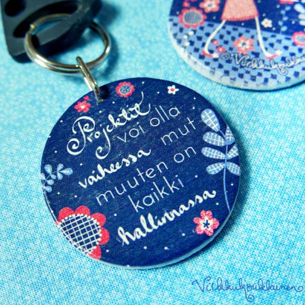 Pyöreä puinen Suomessa valmistettu Virkkukoukkusen suunnittelema sininen avaimenperä kivalla tekstillä.