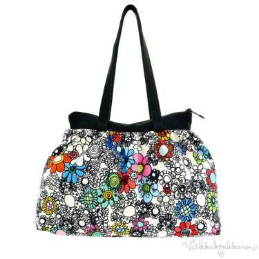 Virkkukoukkusen suunnittelema hauskan mallinen napakka canvas-laukku. Värikäs kukkaralla kuosinen olkalaukku on Suomessa tehty.