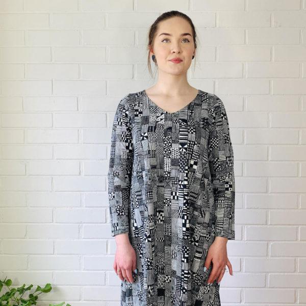 Virkkukoukkusen mustavalkoinen A-linjainen lempileninki trikoomekko domino kuosilla. Kotimaisessa mukavassa mekossa on pitkät hihat ja V-pääntie.