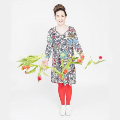 Virkkukoukkusen värikäs A-linjainen lempileninki trikoomekko maksikukkaralla kuosilla. Kotimaisessa mukavassa mekossa on pitkät hihat ja V-pääntie.