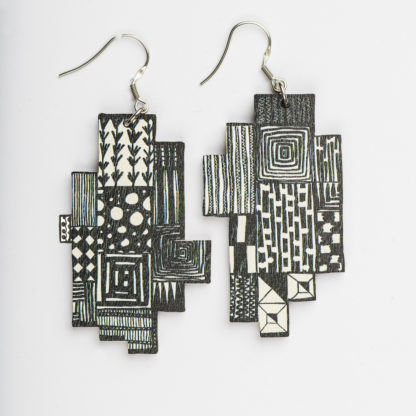 Kauniit Suomessa suunnitellut ja valmistetut puiset korvakorut Domino-kuosilla.