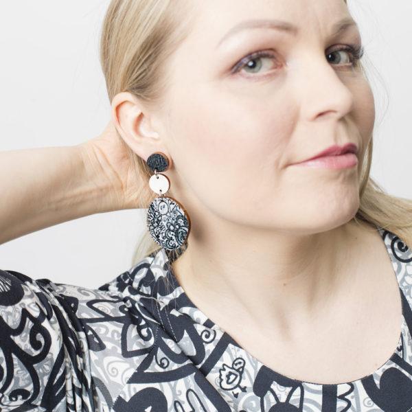 Kauniit Suomessa suunnitellut ja valmistetut puiset roikkuvat korvakorut mustavalkoisella Kumu-kuosilla.