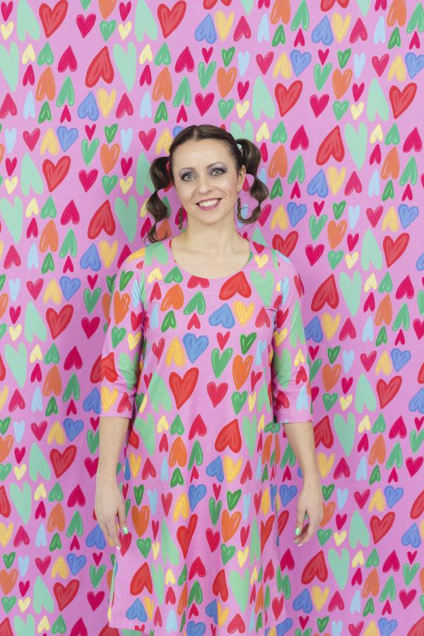 Kotimainen Virkkukoukkusen 3/4-hihainen Kiva-mekko U-pääntiellä pinkkipohjaisella Hertta kuosilla, jossa on monenvärisiä sydämiä.