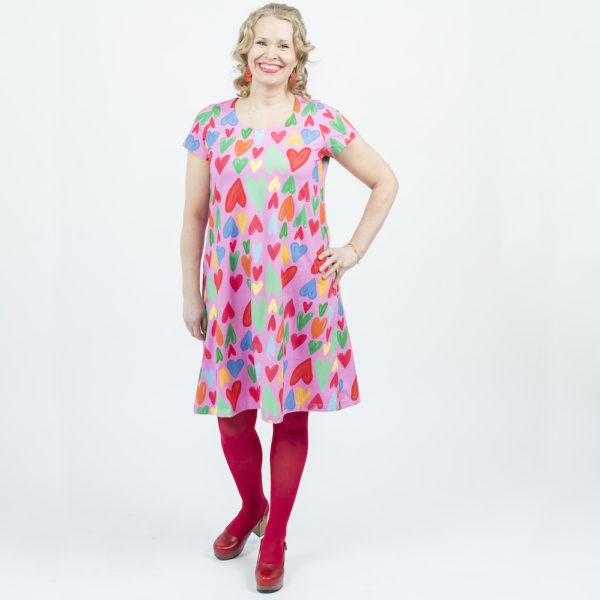 Kotimainen Virkkukoukkusen lyhythihainen Kiva-mekko U-pääntiellä ja pinkillä Hertta-kuosilla.