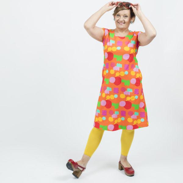 Kotimainen Virkkukoukkusen lyhythihainen Kiva-mekko U-pääntiellä ja hauskalla oranssipohjaisella Lempukka -kuosilla.