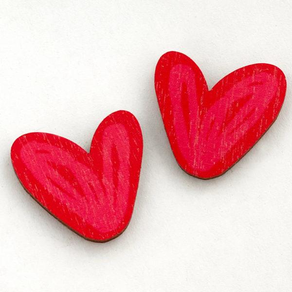 Kauniit Suomessa suunnitellut ja valmistetut puiset nappikorvakorut Hertta-kuosin punaisilla sydämillä.