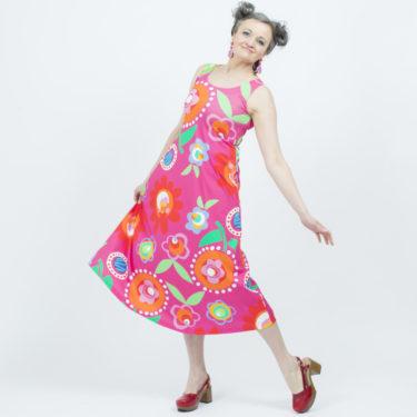Virkkukoukkusen kaunis A-linjainen trikoomekko pinkkipohjaisella Kukkaa pukkaa -kuosilla. Kotimainen mukavan tuntuinen hellemekko on hihaton ja siinä on O-pääntie.