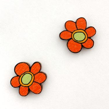 Kauniit Suomessa suunnitellut ja valmistetut puiset nappikorvakorut Kukkaralla-kuosin oransseilla kukilla.