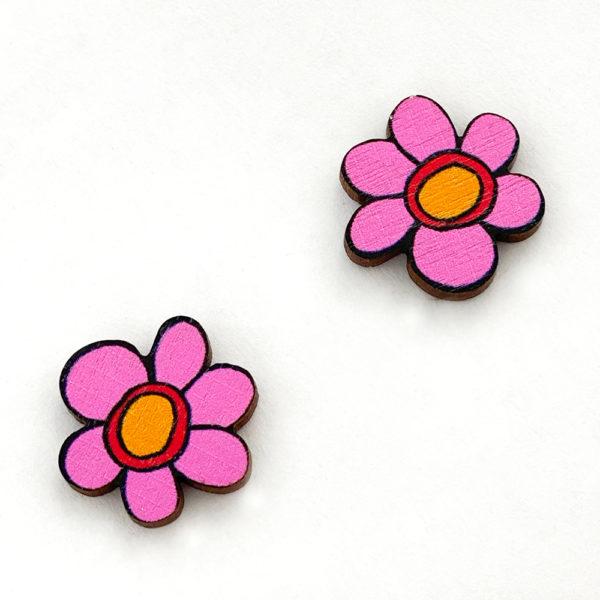 Kauniit Suomessa suunnitellut ja valmistetut puiset nappikorvakorut Kukkaralla-kuosin pinkeillä kukilla.