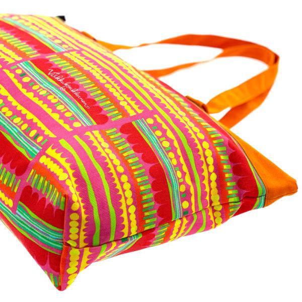 Virkkukoukkusen suunnittelema Suomessa tehty Reilu-laukku vetoketjullisella sisätaskulla. Kuosina iloisen värikäs Optimisti oransseilla kahvoilla.