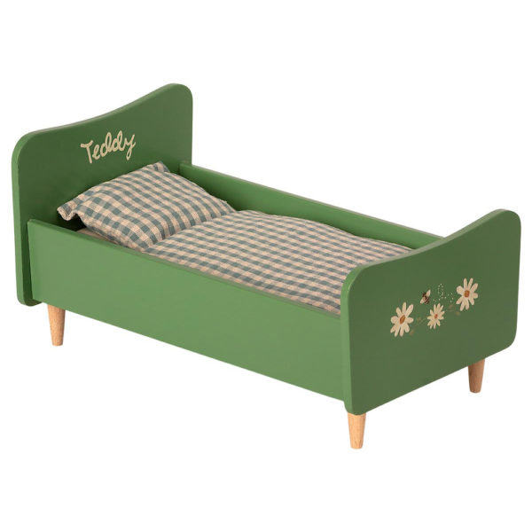 Mailegin vihreä puinen sänky ruudullisilla petivaatteilla.