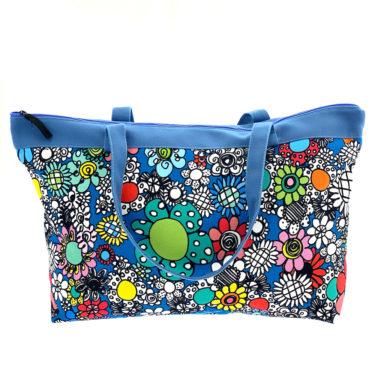 Virkkukoukkusen suunnittelema Suomessa tehty Reilu-laukku vetoketjullisella sisätaskulla. Kuosina kaunis musta-valko-värikäs Kukkaralla sinisellä pohjalla ja sinisillä kantohihnoilla.