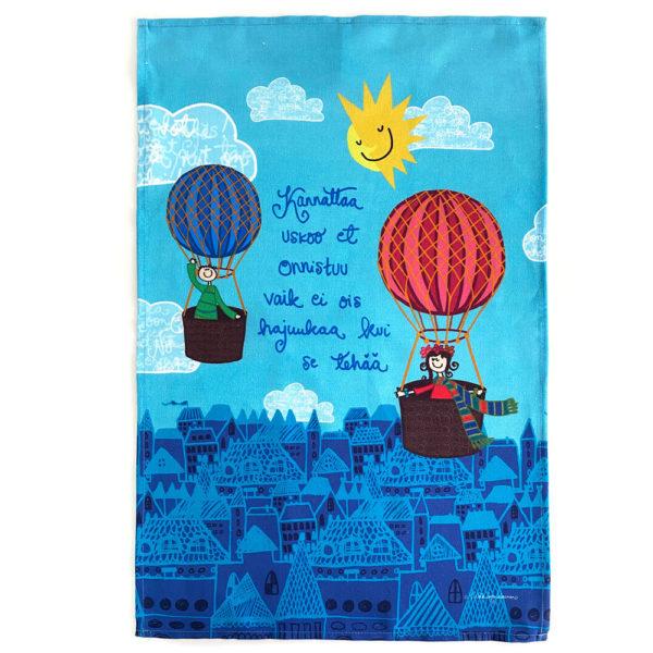 """Kotimainen Virkkukoukkusen ihana puolipellavainen keittiöpyyhe turkoosilla kuvalla jossa seikkailee kuumailmapalloilevat tyttö ja poika ja """"Kannattaa uskoo et onnistuu vaik ei ois hajuukaa kui se tehää""""-tekstillä."""