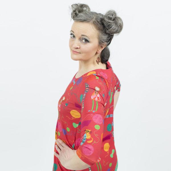 Kotimainen Virkkukoukkusen 3/4-hihainen Kiva-mekko U-pääntiellä ja hauskalla punapohjaisella Kässä-kuosilla, jossa seikkailee neulojia, virkkaajia ja värkkääjiä.