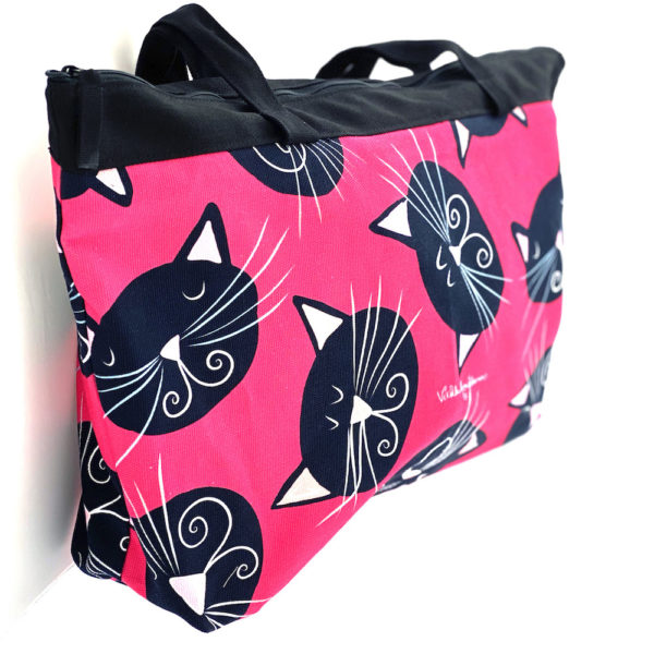 Virkkukoukkusen suunnittelema Suomessa tehty Reilu-laukku vetoketjullisella sisätaskulla. Pinkillä Mustat kissat -kuosilla ja tekstillä.