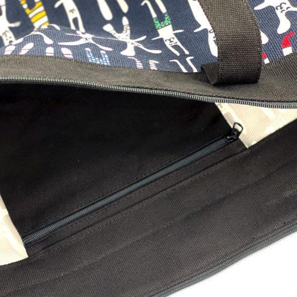 Virkkukoukkusen suunnittelema Suomessa tehty Reilu-laukku vetoketjullisella sisätaskulla. Mustavalkovärikkäällä Pukeutuneet puput -kuosilla.