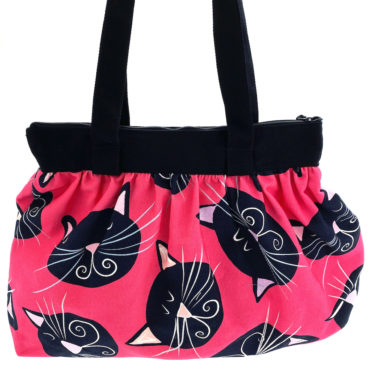 Virkkukoukkusen suunnittelema Suomessa tehty Sumpsa-laukku vetoketjullisella sisätaskulla. Pinkillä Mustat kissat -kuosilla.