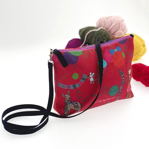 Ihana Virkkukoukkusen vuoritettu canvas-laukku pitkällä olkahihnalla. Veska olkalaukku on valmistettu Suomessa. Kuosina punainen Kässä.